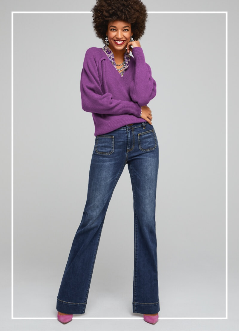 Model wearing the Luxury Pullover in Violet, the Trifle Top in Plum Floral, and the Patch Pocket denim in Trader Wash.